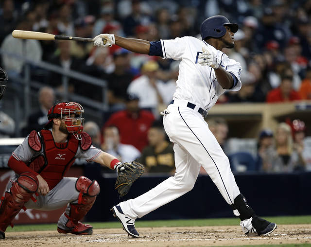 CORRECTS ID TO FRANCHY CORDERO, NOT CORDOBA - San Diego Padres' Franchy Cordero, right, hits a two-run home run with Cincinnati Reds catcher Tucker Barnhart watching during the second inning of a baseball game in San Diego, Monday, June 12, 2017. (AP Photo/Alex Gallardo)