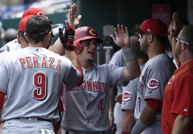 Cincinnati Reds' Scooter Gennett (4) celebrates in the dugout with Jose Peraza (9) and others after he scored during the first inning of a baseball game against the Washington Nationals, Sunday, June 25, 2017, in Washington. (AP Photo/Nick Wass)