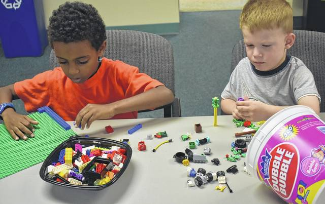 Yonas Brakefield, left, and his brother Isaiah get to work on their Lego projects at the Wilmington Public Library's Lego Club on Wednesday.