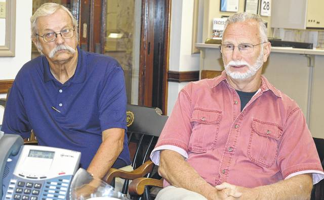 From left, Board of Elections member Joe D. Daugherty and Board Chairperson Steve E. Fricke approach county commissioners with a new idea for a location — after modifications — to store voting equipment.