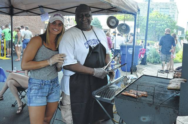 Carlos Roberts was manning a grill at Friday night's 3rd Friday Mural Party at the parking lot next to the General Denver. He was assisted by Miquela Santoro. The featured live music was the Lebanon, Ohio band Dirty Water Dog which plays classic rock and blues.