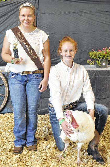 The project of Jozie Jones, right kneeling, earns the distinction of Grand Champion Market Turkey at the Clinton County Fair. Jones is joined in the photograph by Poultry Queen Chloe Caplinger.