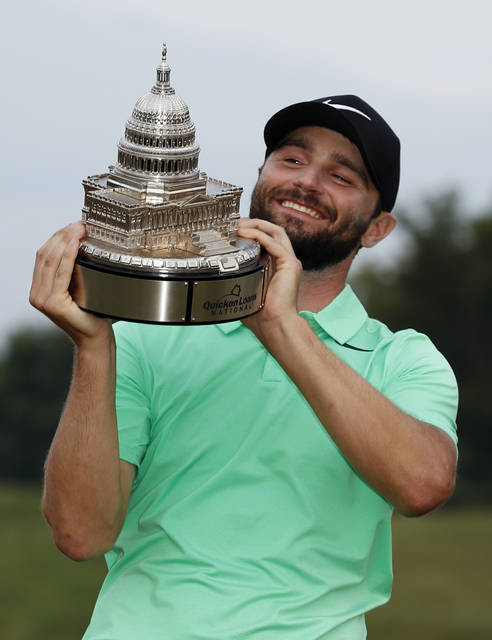 Kyle Stanley holds the trophy after the Quicken Loans National golf tournament, Sunday, July 2, 2017, in Potomac, Md. Stanley won in a playoff. (AP Photo/Alex Brandon)