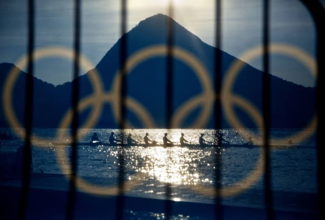FILE - In this Aug. 7, 2016, file photo, rowers are seen through a screen decorated with the Olympic rings as they practice at the rowing venue in Lagoa at the 2016 Summer Olympics in Rio de Janeiro, Brazil. The Olympic Channel, a new Olympic-themed television network makes its debut on Saturday, July 15. (AP Photo/David Goldman, File)