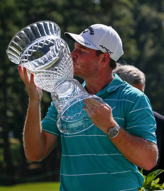 Grayson Murray celebrates by kissing the trophy after winning the Barbasol Championship golf tournament, Sunday, July 23, 2017, in Opelika, Ala. (AP Photo/Butch Dill)