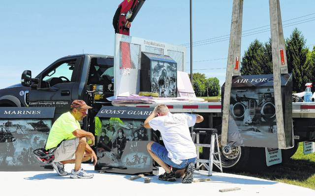 Workers from Laser Imaging & Design set granite markers in place for the Clinton-Massie Veterans Memorial located near the high school on Lebanon Road.