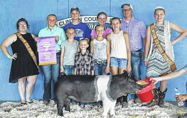 In the Open Swine Show, Grand Overall went to Kennedy Thompson. From left are: back row, Pork Queen Cassie Parks, Kennedy Thompson holding the banner, Adam Thompson, Anne Thompson, show judge Kevin Wendt and Pork Princess Madison Bronner; and front row, Ella Thompson, Juliana Diels, Lauren Diels and Caroline Diels.