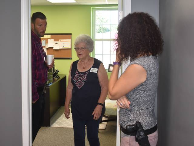 New Life Clinic Board Member Doris Caldwell, center, gives juvenile probation officers Adam Green, left, and Deanne Whalen a tour of their facilities Tuesday. The event was a way for people to get a look at what New Life Clinic to offer inside their South South Street location.