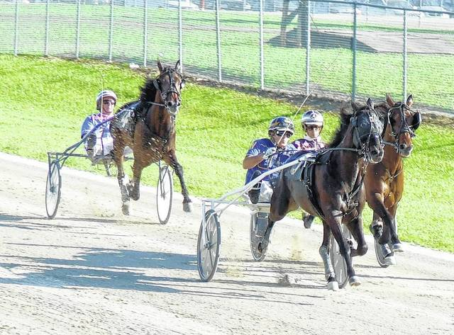 Dark Ruler, driven by Bryan Weaver (middle driver), hit the wire first in the 10th race Sunday at the Clinton County Fair. At the left is runnerup Hunter's Dutchboy, driven by Hugh Beatty. Behind Dark Ruler is third-place finisher Rose Run Spencer, driven by Jeff Nisonger.