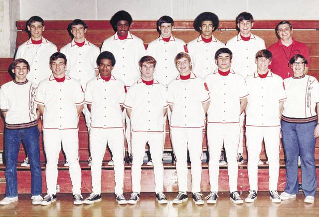 """The 1972-73 Wilmington High School varsity boys basketball team finished with an 11-9 record. That mark included two tournament games — a win over Dayton Belmont and a loss to Dayton Roth. Tim Wilson and Robert Raizk were first-team All-South Central Ohio League while Brad Halley and Tim Haley were given honorable mention All-SCOL. Wilmington was 1-18 the previous season. Among the '72-'73 highlights, Raizk had 34 points on 15 of 23 shooting in a win at McClain. In that game, Against Bellbrook, Wilson had 20 points, 15 rebounds and 8 blocked shots. Bill McClary handed out 11 assists. Wilson had three 18-rebound games, a 23-rebound game and a 24-rebound game. None were his season best, though. Timbo was credited with 28 rebounds in a 61-59 win at Richardson Place against McClain. In a 66-61 loss at Circleville, WHS was whistled for 31 fouls — four Hurricane fouled out — while the Tigers had 13 fouls. WHS made 14 of its last 15 free throws in a 73-67 win over the Blue Lions. Wilmington stopped East Clinton's 14-game win streak with a 58-57 victory. In the photo, the 1972-73 Wilmington High School varsity boys basketball team, from left to right, front row, Tim Gillespie, Brad Halley, Derwin Baker, Kip Collins, Bill McClary, Robert Raizk, Kyle Lundy, Jeff Phillips; back row, Jeff Early, Dave Hinman, Tim """"Timbo"""" Wilson, Tim Haley, Ralph Harding, Randy Reeder, head coach Buddy Bell."""