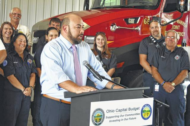 At the podium, Speaker of the Ohio House of Representatives Cliff Rosenberger (R-Clarksville) speaks Thursday at his Clinton County hometown during a ceremony for a three-story burn tower to be built there for preparing and training firefighters. At the event, Rosenberger announced the newly signed state budget includes $150,000 for new training equipment to go along with the facility, which is targeted for completion in November, weather permitting. Partners in the project include Southern State Community College and Sinclair Community College in Dayton, which has a Fire Science Technology Department. Fire departments in multiple counties are expected to utilize the facility for new and current first responders. The burn tower at the Clinton-Warren Joint Fire & Rescue District Training Center was made possible through the Ohio Capital Budget. In the photograph's background are part of the first-responder roster of the Clinton-Warren Joint Fire District & EMS.