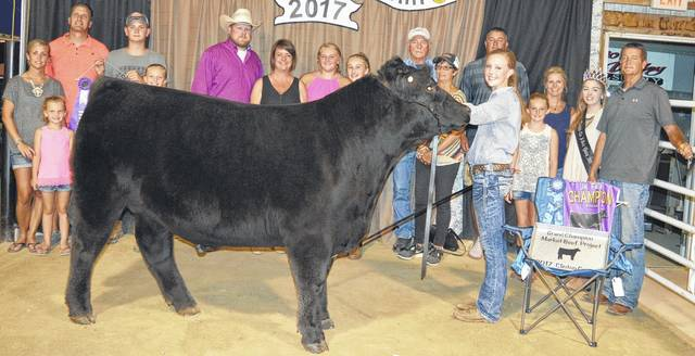 Anne Thompson of the Liberty Livestock 4-H Club stands alongside her Grand Champion Market Beef Project (and champion market steer), which had a show weight of 1,373 pounds. Also pictured are Anne Thompson's family, Clinton County Junior Fair Queen Bridgette Thompson and show judge Clayton Cook in a cowboy hat.