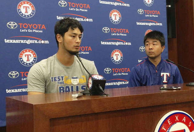 Former Texas Rangers pitcher Yu Darvish, left, responds to a question during a news conference as his translator Hideaki Sato prepares to translate regarding his trade to the Los Angeles Dodgers before a baseball game against the Seattle Mariners on Monday, July 31, 2017, in Arlington, Texas. (AP Photo/Tony Gutierrez)