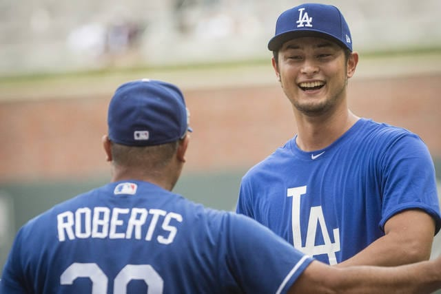 Los Angeles Dodgers' Yu Darvish, right, talks to manager Dave Roberts before a baseball game against the Atlanta Braves, Wednesday, Aug. 2, 2017, in Atlanta. Darvish was recently acquired from the Texas Rangers. (AP Photo/John Amis)