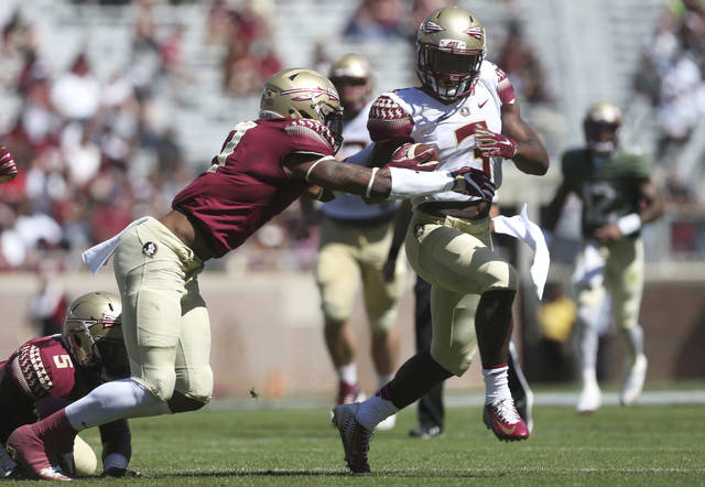 FILE - In this April 8, 2017, file photo, Florida State freshman running back Cam Akers tries to break away from Stanford Samuels III during the NCAA college football team's Garnet and Gold spring game in Tallahassee, Fla. Akers presence could help Florida State withstand the loss of Minnesota Vikings second-round draft pick Dalvin Cook, the Seminoles' career rushing leader. (Joe Rondone/Tallahassee Democrat via AP, File)
