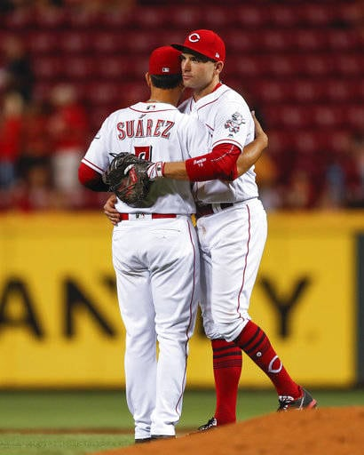 Cincinnati Reds third baseman Eugenio Suarez, left, and first baseman Joey Votto, right, celebrate the team's 8-3 win over the San Diego Padres in a baseball game Wednesday, Aug. 9, 2017, in Cincinnati. (AP Photo/John Minchillo)