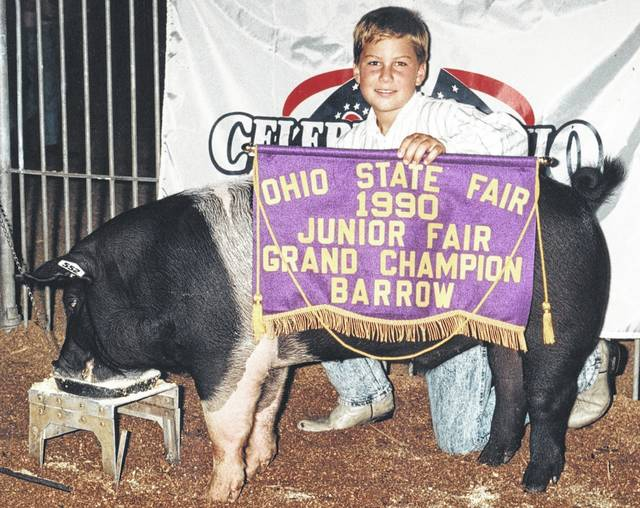 Brad Flint, then 10, proudly displays his 1990 Ohio State Fair grand champion market barrow. Afterward he sold the cross barrow at the Sale of Champions Livestock Auction, which observes its 50th anniversary this Sunday in Columbus.