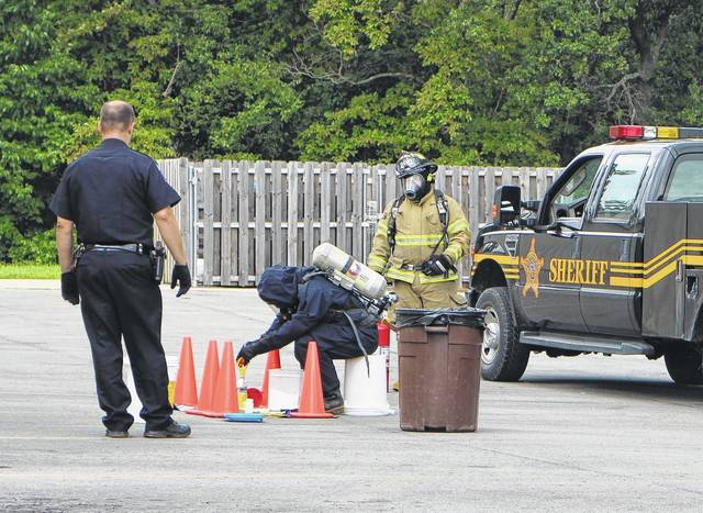 Investigators examine an alleged one-pot meth lab in a parking lot on North High Street Friday afternoon.