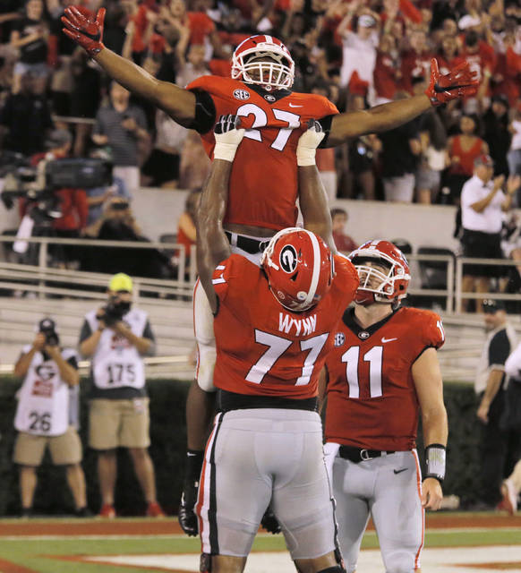 Georiga running back Nick Chubb (27) celebrates after scoring during second half against Mississippi State, as he is lifted by offensive tackle Isaiah Wynn (77) as quarterback Jake Fromm (11) watches, during an NCAA college football game Saturday, Sept. 23, 2017, in Athens, Ga. (Bob Andres/Atlanta Journal Constitution via AP)