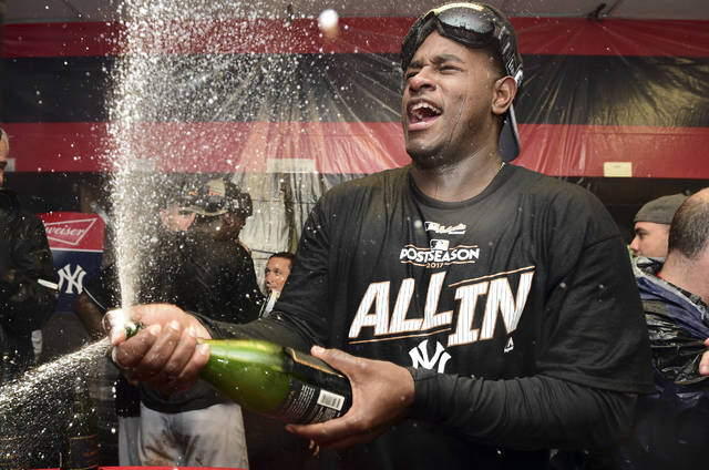 New York Yankees starting pitcher Luis Severino sprays sparkling wine in the locker room the Yankees defeated the Cleveland Indians 5-2 in Game 5 of a baseball American League Division Series, early Thursday, Oct. 12, 2017, in Cleveland. The Yankees advanced to the ALCS. (AP Photo/David Dermer)