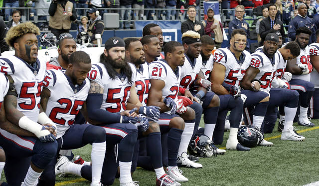 Houston Texans players kneel during the singing of the national anthem before an NFL football game against the Seattle Seahawks, Sunday, Oct. 29, 2017, in Seattle. (AP Photo/Elaine Thompson)