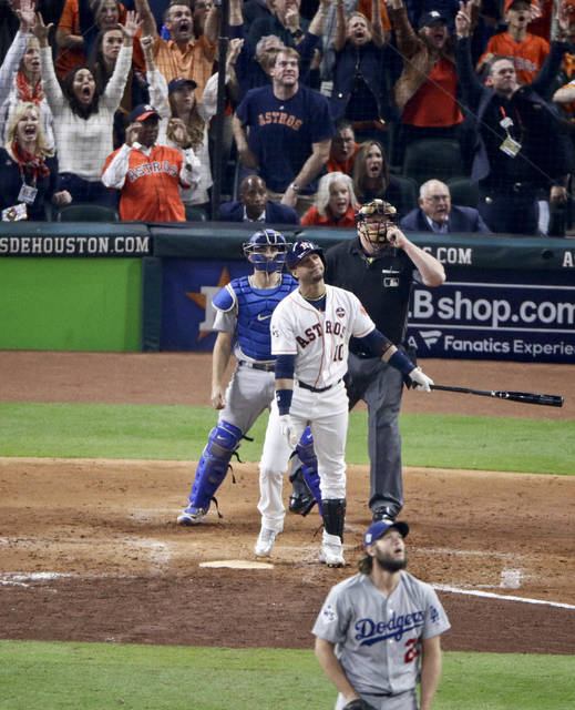 Houston Astros' Yuli Gurriel watches his three-run home run off Los Angeles Dodgers starting pitcher Clayton Kershaw during the fourth inning of Game 5 of baseball's World Series Sunday, Oct. 29, 2017, in Houston. (AP Photo/Charlie Riedel)