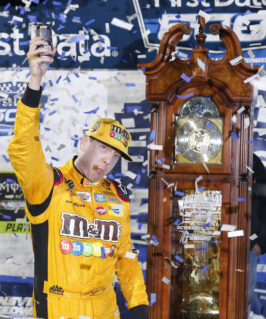 Kyle Busch celebrates after winning the NASCAR Cup series auto race at Martinsville Speedway in Martinsville, Va., Sunday, Oct. 29, 2017. The grandfather clock is the winner's trophy. (AP Photo/Steve Helber)