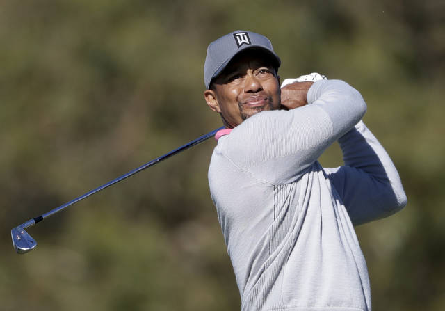 FILE - In this Friday, Jan. 27, 2017 file photo, Tiger Woods watches his tee shot on the ninth hole of the North Course during the second round of the Farmers Insurance Open golf tournament at Torrey Pines Golf Course in San Diego. Tiger Woods is returning to competition at his holiday tournament in the Bahamas the week after Thanksgiving, Thursday, Nov. 23, 2017. (AP Photo/Gregory Bull, File)