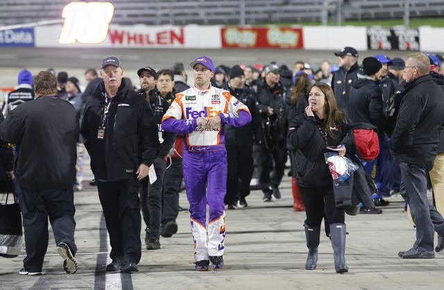 Denny Hamlin, center, leaves the track after the NASCAR Cup series auto race at Martinsville Speedway in Martinsville, Va., Sunday, Oct. 29, 2017. Hamlin wrecked with Chase Elliott during the last few laps of the race. (AP Photo/Steve Helber)