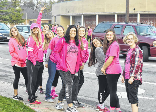 The Clinton-Massie High School volleyball team stands across from the Boyd Regional Cancer Center while wearing pink to raise awareness for breast cancer during the Brake for Breakfast on Tuesday morning.