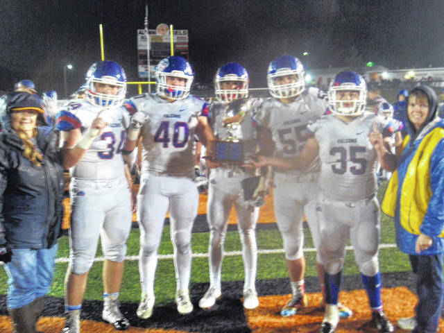 Kiwanians Terri Thobaben (far left) and Kim Hiatt (far right) present Clinton-Massie football captains with the annual Backyard Bash trophy for winning Friday night's game against Wilmington. The captains are, from left to right, Weston Trampler, Trey Uetrecht, Luke Richardson, Sam Brothers and Cody Collingham. The Wilmington Kiwanis Club sponsors the Backyard Bash Trophy.