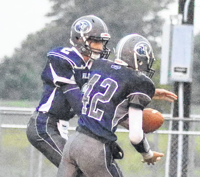 Blanchester quarterback Brayden Sipple (left) hands to Blake Richard during a game earlier this season.