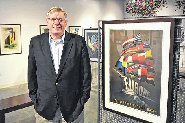"""Sam Stratman stands in the Quaker Heritage Center gallery next to his favorite of the 26 Marshall Plan posters titled """"All our colours to the mast."""""""
