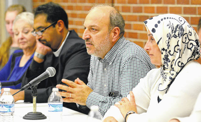 Taking part in a three-faiths conversation on the treatment of refugees are, from left, Salma Albezreh (partly hidden), Sandy Spinner, Rev. Canon Manoj Zacharia, and Dr. Ashraf Traboulsi and his wife.