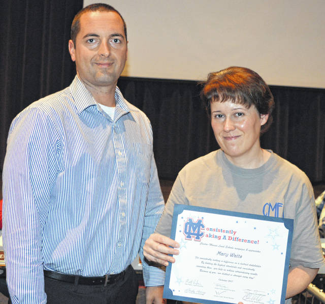 Clinton-Massie Local Schools Board of Education Vice President Chris Harrison, left, presents high school Spanish teacher Mary Watts with a Consistently Making A Difference Award.