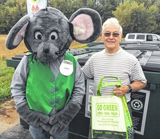 """Thomas Hovan was the first culprit in the annual Get Caught Recycling Campaign. Buster the Mouse, from the Clinton County Solid Waste District, caught Thomas """"green-handed"""" putting the proper recyclables into the community drop-off recycling container located at Streber's Market in New Vienna. This year's Get Caught Recycling theme is Rest & Relaxation. For his efforts in practicing the 3 R's, Thomas received several recycled content prizes, including a hammock, shopping bag, and other such prizes. Don't miss out on this chance to win great prizes by simply recycling household items such as bottles, jars, and newspapers. For a list of the local recycling drop-off locations and acceptable materials, visit the SWMD's website at www.co.clinton.oh.us/recycling. There are still three weeks left in the campaign, so be on the lookout … you could be the next person caught green-handed"""
