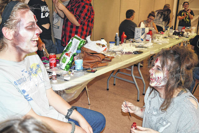 Prior to a Zombie 5K run Saturday evening at Laurel Oaks, where zombie characters lurked along the running course, makeup was applied to students and volunteers so they would look the part. Two zombies were caught laughing during the makeup phase. In the foreground from left are Chris Slone and Aubrey Wile, both of whom are Oaks students with McClain as their home school.