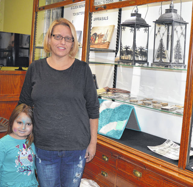 "Olde Barn Door owner-operator Rebecca ""Becca"" Bennett stands inside the retail store in downtown Wilmington. She is joined by her granddaughter Michelle Nakata, who has blue makeup on her face in preparation for a preschool Halloween Day trick-or-treat trip to the city building. She soon will get dressed up in a mermaid outfit."