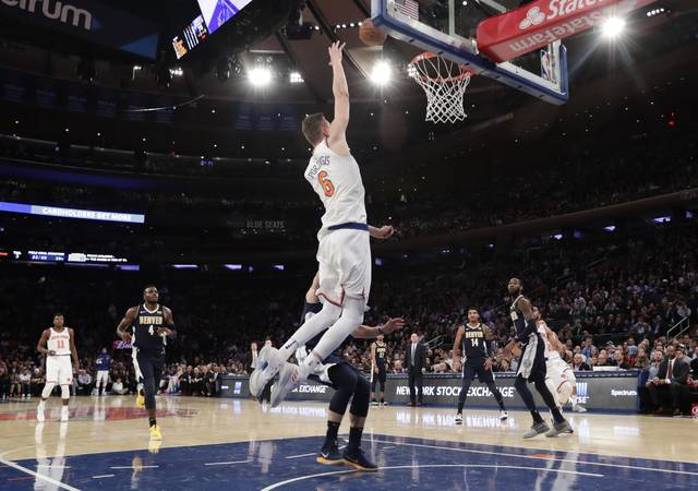 New York Knicks' Kristaps Porzingis (6) catches a lob pass from Courtney Lee for a dunk in front of Denver Nuggets' Wilson Chandler, blocked from view, during the second half of an NBA basketball game Monday, Oct. 30, 2017, in New York. The Knicks won 116-110. (AP Photo/Frank Franklin II)