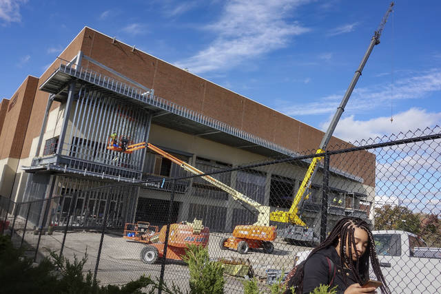 A student passes along perimeter fencing around Fifth Third Arena, home of the University of Cincinnati Bearcats basketball program, as major renovations continue, Tuesday, Oct. 31, 2017, in Cincinnati. The Bearcats will spend a season playing home games across the river in northern Kentucky, hoping their deep and versatile team settles in quickly to the new surroundings. (AP Photo/John Minchillo)