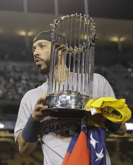Houston Astros' Marwin Gonzalez holds the championship trophy after Game 7 of baseball's World Series against the Los Angeles Dodgers Wednesday, Nov. 1, 2017, in Los Angeles. The Astros won 5-1 to win the series 4-3. (AP Photo/David J. Phillip)