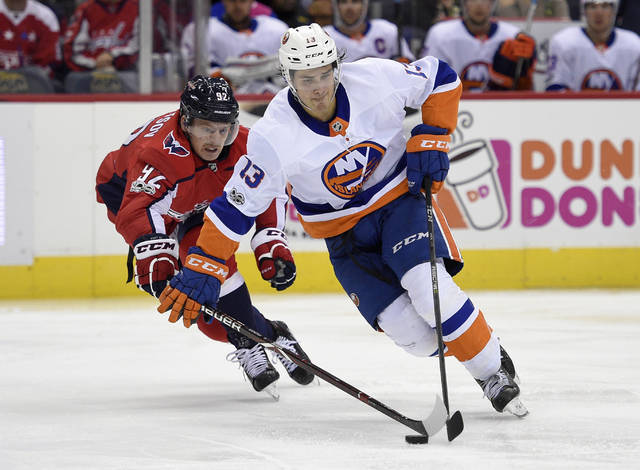 """FILE - In this Nov. 2, 2017, file photo, New York Islanders center Mathew Barzal (13) skates with the puck against Washington Capitals center Evgeny Kuznetsov (92), of Russia, during the second period of an NHL hockey game in Washington. It's the best phrase a young NHL player can hear, even better than being told he's made the team. Get a place. Making the opening night roster is certainly an accomplishment, though it can be fleeting. The time-honored tradition of a coach or general manager giving a player permission to check out of the hotel and find a place to live means he's sticking around for a long time, if not the entire season. There's value in getting that message from an organization well before the 28-day mark, as Islanders rookie Barzal found out. """"That kind of just made me comfortable, just knowing I have an opportunity to be here for a little while or they like what I've been doing so far,"""" said Barzal. (AP Photo/Nick Wass, File)"""