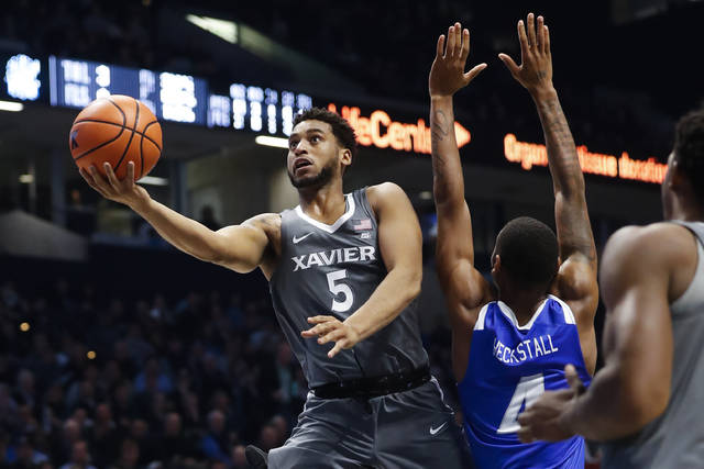 Xavier's Trevon Bluiett (5) shoots against Hampton's Greg Heckstall (4) in the second half of an NCAA college basketball game, Monday, Nov. 20, 2017, in Cincinnati. Xavier won 96-60. (AP Photo/John Minchillo)