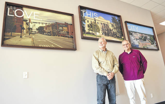 From left, Dove Church Senior Elder Steve Fricke and Pastoral Elder Dave Hinman stand in the roomy lobby area in front of large photographs of Wilmington.