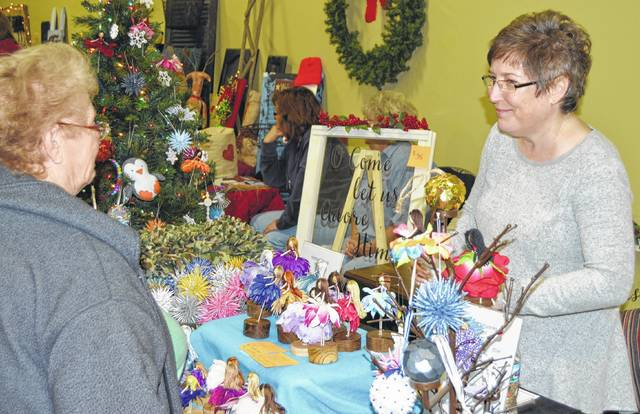 At last year's event, Rosemary Chandler, left, talks with Lynn Bush about the paper ornaments and flower dolls during the Christmas Around Sabina Town.