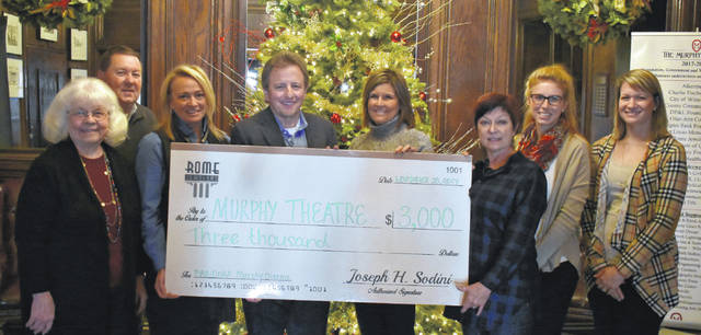 Rome Jewelers in Wilmington presented a $3,000 donation to the Murphy Theatre on Monday. The money was raised through selling a special Murphy Pandora charm. For every charm purchased, $25 would be donated. Shown are Rome Jewelers representatives as well as representatives of the Murphy. From left are Jennifer Hollon, Scott Holmer, Leslie Keller-Biehl, Joe and Janine Sodini, Maretta Alden, Marci Meintel and Liz Doyle.