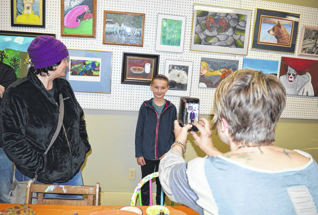 A Fall Show was held Friday evening consisting of a collection of artwork by youth who are students at Thorngren Studio Arts in downtown Wilmington. Mary Beth Thorngren, right foreground, takes a photo of her art student Ethan Robinett, 11, who stands in front of his work showing a plate of cookies and a glass of milk. Participating young artists included Michael Shobe, Grace Helms, Jocelyn Engel, Deonna Harlow, Nathan Wood, Lilly Middleton, Dillon Bailey, Brian Poston, Chloe Mason, Sydney Walls, Mackenzie Pyle, Steven Collins, Collin Wood and Ethan Robinett. The event was well attended.