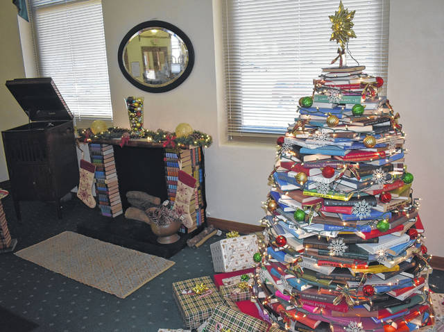 The Wilmington Public Library adds a warm fireplace made of books to their festive display, including their Christmas tree of books.