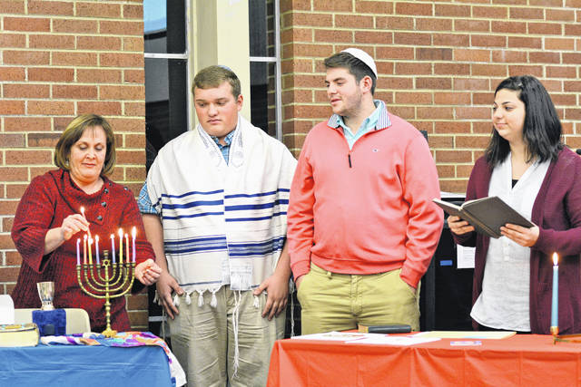 Sophomore Eli Feuer, donning a yarmulke, and sophomore Sarah Lebowitz all explain Hanukkah's eight-day, eight-night Festival of Lights as Ellen Simkin, a Jewish guest from Cincinnati, lights a menorah.
