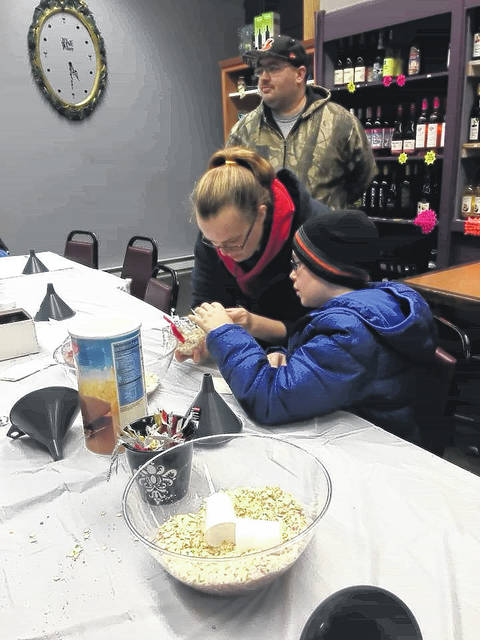 At South Street Wine Make and Take, creating a reindeer food ornament as Brittnie Sexton assists nephew Seth, 11, the grandson of Karen Sexton.